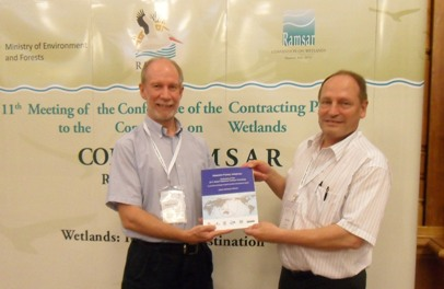 The presentation to Olivier Biber, the governmental Swiss Federal Office, from Spike Millington, EAAFP at Ramsar COP11 © EAAFP